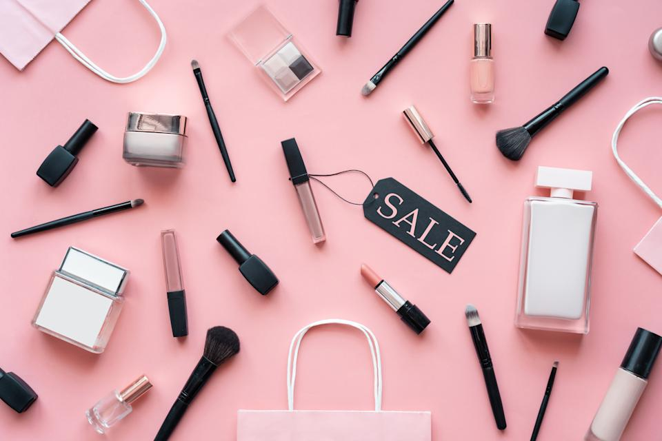 Cosmetic and perfume female products accessories promotion offer with sale tag beauty makeup fashion items objects set with shopping bags on pink table background, flat lay, top view above