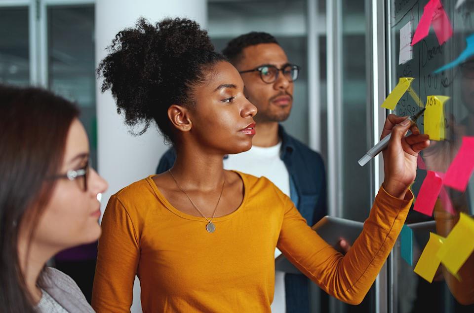 Executives looking at businesswoman writing on adhesive notes stuck over glass