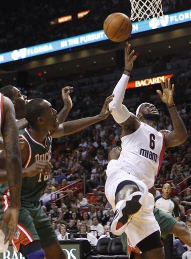 Miami Heat's LeBron James (6) attempts a shot as Milwaukee Bucks' Luc Mbah a Moute (12) looks on during the first half of an NBA basketball game, Sunday, Jan. 22, 2012, in Miami. (AP Photo/Lynne Sladky)