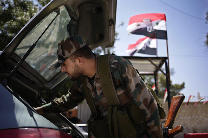FILE - In this Wednesday, Aug. 21, 2013 file photo, a Syrian military soldier checks the trunk of a car at a check point on Baghdad street in Damascus, Syria. The Syrian flag with the photo of President Bashar Assad is seen at background. The signs would all seem bad for President Bashar Assad. Blasts echo all day long over the Syrian capital as troops battle rebels entrenched on its eastern doorstep. The government admits the economy is devastated. And now allegations of a horrific chemical attack have given new life to calls for international action against his regime.(AP Photo/Hassan Ammar)