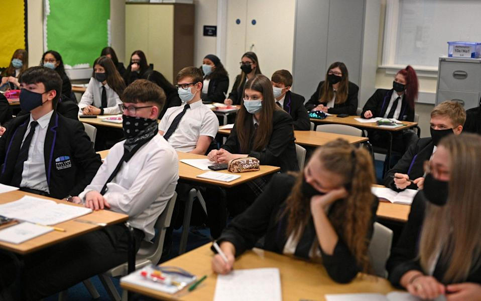 Year 11 students, wearing face coverings, take part in a GCSE maths class at Park Lane Academy in Halifax, northwest England on March 8, 2021 as schools reopen following the easing of lockdown restrictions - OLI SCARFF /AFP