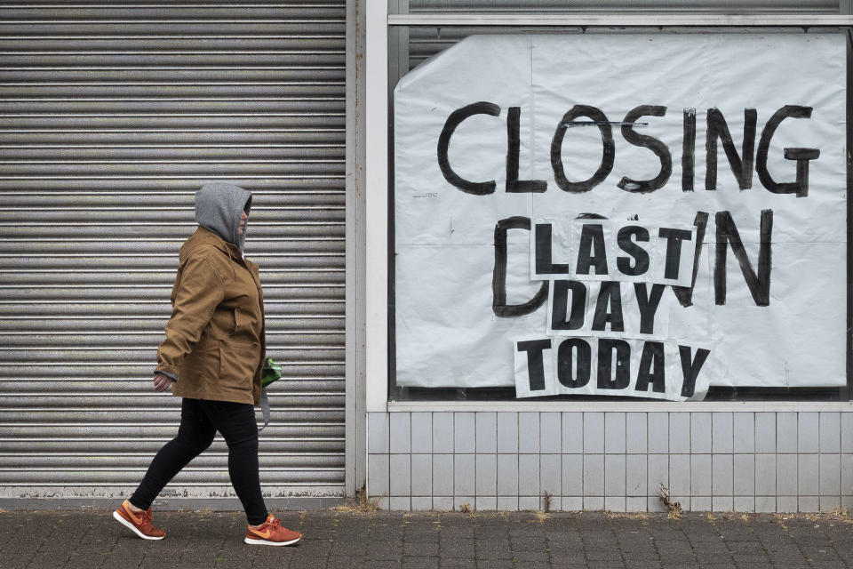 ABERDARE, UNITED KINGDOM - JUNE 10: A woman walks passed a closed-down shop on June 10, 2020 in Aberdare, United Kingdom. The Welsh government has further relaxed COVID-19 lockdown measures this week, allowing people from different households to meet up outside while maintaining social distancing. Schools have remained closed and those who have been advised to shield at home can go outside again but have been told to avoid shopping. (Photo by Matthew Horwood/Getty Images)