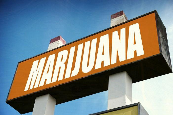 A large marijuana sign in front of a dispensary store.