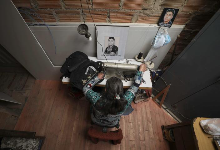 Doris Tejada, the mother of Oscar Alexander Morales, works at her home with a photo of her son who disappeared on New Year's eve 2007, next to her in Soacha, Colombia, Thursday, April 8, 2021. The case of Tejada's son Oscar, who was 26 years old when he disappeared, was accepted in the Special Jurisdiction for Peace, the court in charge of judging the facts of the bloody and long-running internal conflict. She has joined the Mothers of Soacha, a group made up of mothers, wives and sisters who demand justice for similar cases. (AP Photo/Fernando Vergara)