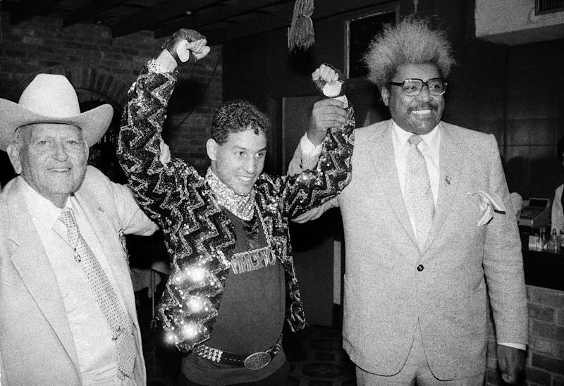 "FILE - In this Dec. 9, 1986 file photo, Hector ""Macho"" Camacho WBC lightweight boxing champion, is escorted by Marty Cohen, left, and boxing promoter Don King, right, during a news conference in New York. Famed Puerto Rican boxer Camacho is clinically brain dead, doctors said Thursday, Nov. 22, 2012, though they said family members were disagreeing on whether to take him off life support. Dr. Ernesto Torres said doctors have finished performing all medical tests on Camacho, who was shot in the face Tuesday night. (AP Photo/David Bookstaver, File)"