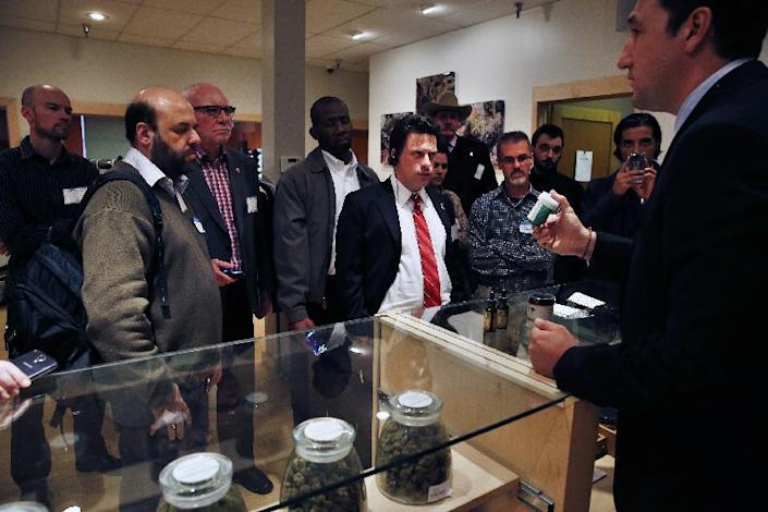 FILE - In this Oct. 23, 2013, Norton Arbelaez, right, the owner of River Rock marijuana dispensary, shows his products to foreign lawmakers, Julio Bango, of Uruguay, second from left, Larry Campbell, of Canada, third from left, and Fernando Belaunzaran, of Mexico, fifth from left, during a tour of his business in Denver. Several foreign lawmakers pushing for drug law reforms at home took a close up look the evolving legal marijuana industry in Colorado. Washington and Colorado passed recreational laws in 2012 to regulate the growth and sale of taxed pot at state-licensed stores. Sales began Jan. 1 in Colorado, and are due to start later this year in Washington. Twenty states and the District of Columbia also now have medical marijuana laws. (AP Photo/Brennan Linsley, File)
