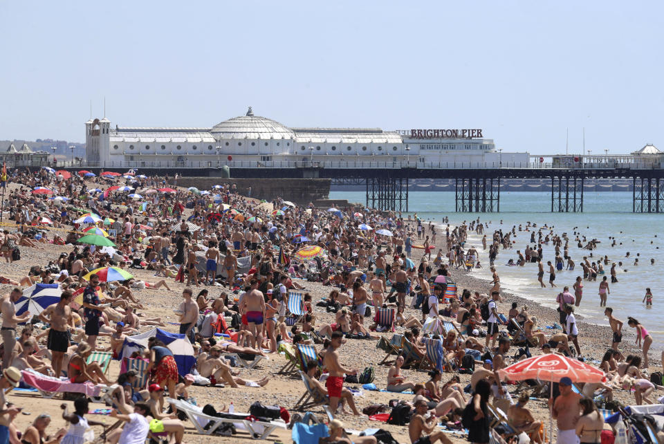Crowds gather as hot weather draws crowds to the beach in Brighton, England, Thursday June 25, 2020. Coronavirus lockdown restrictions are being relaxed but people should still respect the distancing requirements between family groups. According to weather forecasters this could be the UK's hottest day of the year, so far, with scorching temperatures forecast to rise even further. (Gareth Fuller/PA via AP)