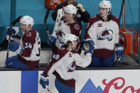 Colorado Avalanche defenseman Samuel Girard, bottom, is congratulated by teammates after scoring against the San Jose Sharks during the third period of an NHL hockey game in San Jose, Calif., Wednesday, March 3, 2021. (AP Photo/Jeff Chiu)