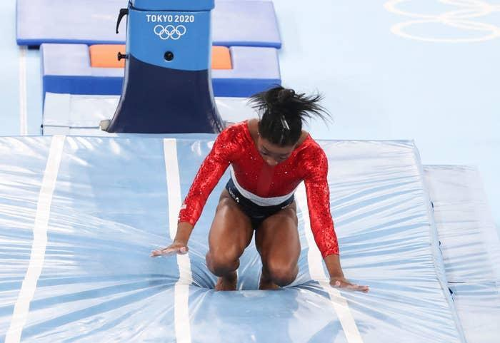 Biles landing her vault with her knees and hands almost touching the ground