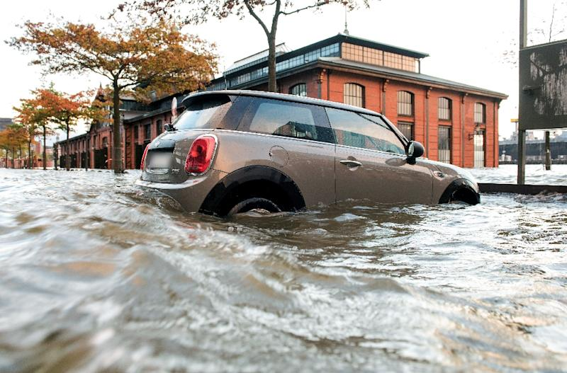 Flood waters surround a car parked in Hamburg's Fish Market district as a storm hits many parts of Germany and cenral Europe