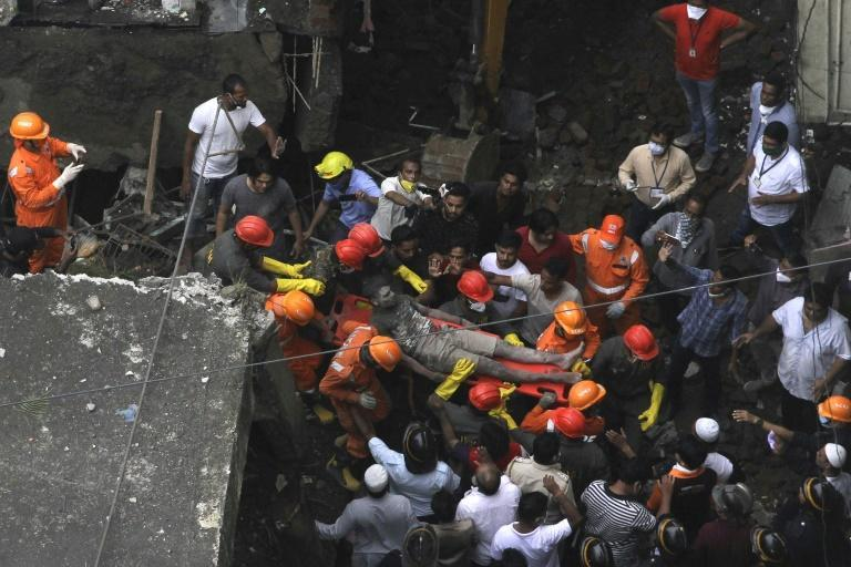 Rescue workers carry a survivor from the rubble of a collapsed three-storey residential building in Bhiwandi