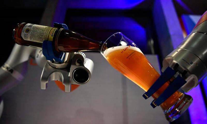 Industrial robot manufacturer Kuka demonstrates two robotic arms pouring a beer for guests at the Summit of the Business20 in Berlin