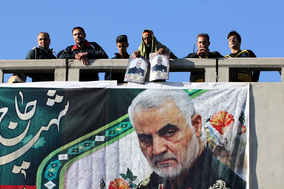 """Iranian mourners stand on a bridge during the final stage of funeral processions for slain top general Qasem Soleimani, in his hometown Kerman on January 7, 2020. - Soleimani was killed outside Baghdad airport on January 3 in a drone strike ordered by US President Donald Trump, ratcheting up tensions with arch-enemy Iran which has vowed """"severe revenge"""". The assassination of the 62-year-old heightened international concern about a new war in the volatile, oil-rich Middle East and rattled financial markets. (Photo by ATTA KENARE / AFP) (Photo by ATTA KENARE/AFP via Getty Images)"""