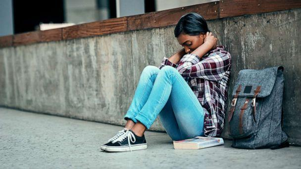 PHOTO: An undated stock photo depicts a young female college student sitting alone on campus. (STOCK PHOTO/Getty Images)