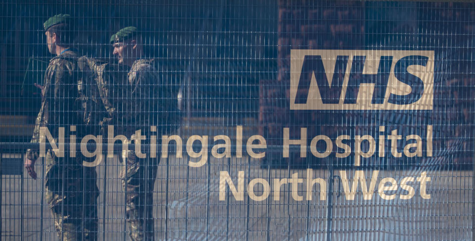 Members of the Military behind hoardings during final preparations at the National Health Service (NHS) Nightingale North West hospital which is now open in Manchester, England, Tuesday April 14, 2020. The Nightingale North West hospital was built in 14-days at the main central hall of the former Manchester Central railway station, and is capable of treating some 750 virus patients.  The highly contagious COVID-19 coronavirus has impacted on nations around the globe, many imposing self isolation and exercising social distancing when people move from their homes. (Peter Byrne / PA via AP)