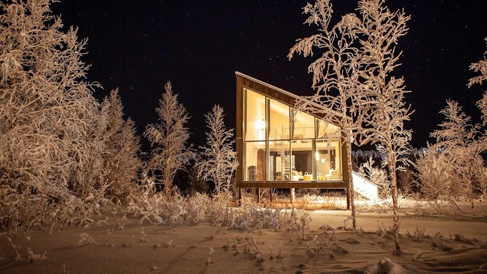"""<em>Game of Thrones</em> hideaway? Warrior den from a Norse saga? Pick-up sticks? The idea for this frosty-donut design in the Swedish Lapland stretches back a decade, but the hotel's opening in January felt like something of an event in a place where time is usually measured in millennia. Created by Bertil Harström, one of the architects behind the quirky Treehotel, and Swedish designer Johan Kauppi, Arctic Bath comprises six jaunty wooden cabins with pared-back interiors of pale pine and Baltic limestone near the edge of the River Lule and a half-dozen larger ones on the tree-lined shore. In the restaurant, smoked wood grouse, cured trout, and slow-cooked reindeer are served by Maarten De Wilde and Kristoffer Åström, the latter known as """"the Sámi chef"""" for taking the community's flavors to kitchens across <a href=""""https://www.cntraveler.com/gallery/places-to-visit-in-sweden-that-arent-stockholm?mbid=synd_yahoo_rss"""" rel=""""nofollow noopener"""" target=""""_blank"""" data-ylk=""""slk:Sweden"""" class=""""link rapid-noclick-resp"""">Sweden</a>. But the real reason to make the pilgrimage is for total immersion in the landscape, whether that's an immune-boosting plunge in the open-air cold tub, forest-bathing in the summer, or ice-skating on the frozen river. The stillness and light feel meditative—during the few hours of daylight in winter, the sky is pink and purple, the only sound is the crunching snow. The grass-covered roofs shift color through the seasons, attracting bees and birds. This is like nowhere else on earth."""