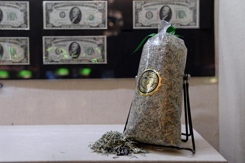 A bag of shredded US currency (R) on display in the exhibition 'The Fed at 100' at the Museum of American Finance December 17, 2013 in New York. These USD bills have been removed from circulation and shredded into confetti. In the background are USD $10 bills from each of the 12 district banks of the Federal Reserve System. The exhibition marks the 100th anniversary of the Federal Reserve System. The Fed was created on December 23, 1913, with the enactment of the Federal Reserve Act, largely in response to a series of financial panics, particularly a severe panic in 1907. Over time, the roles and responsibilities of the Federal Reserve System have expanded and its structure has evolved. Events such as the Great Depression were major factors leading to changes in the system. AFP PHOTO/Stan HONDA (Photo credit should read STAN HONDA/AFP/Getty Images)