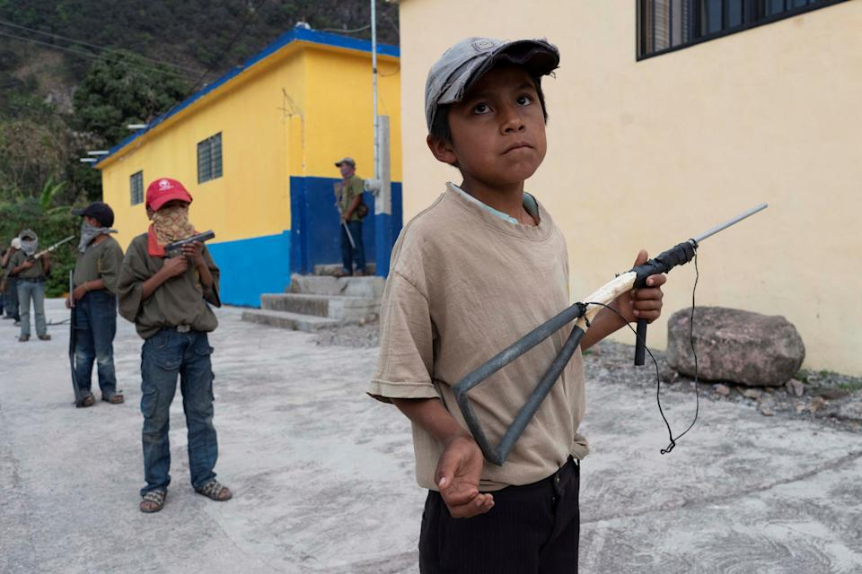 Children hold toy guns as they demonstrate newly learnt skills from military-style weapons training, to a Reuters journalist, in Ayahualtempa, Mexico, February 3, 2020. REUTERS/Alexandre Meneghini      SEARCH