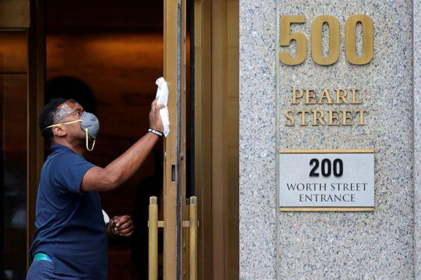 PHOTO: A worker cleans the entrance to the Manhattan Federal Court, during the arraignment hearing of Ghislaine Maxwell for her role in the sexual exploitation and abuse of minor girls by Jeffrey Epstein, in New York City, on July 14, 2020. (Mike Segar/Reuters)