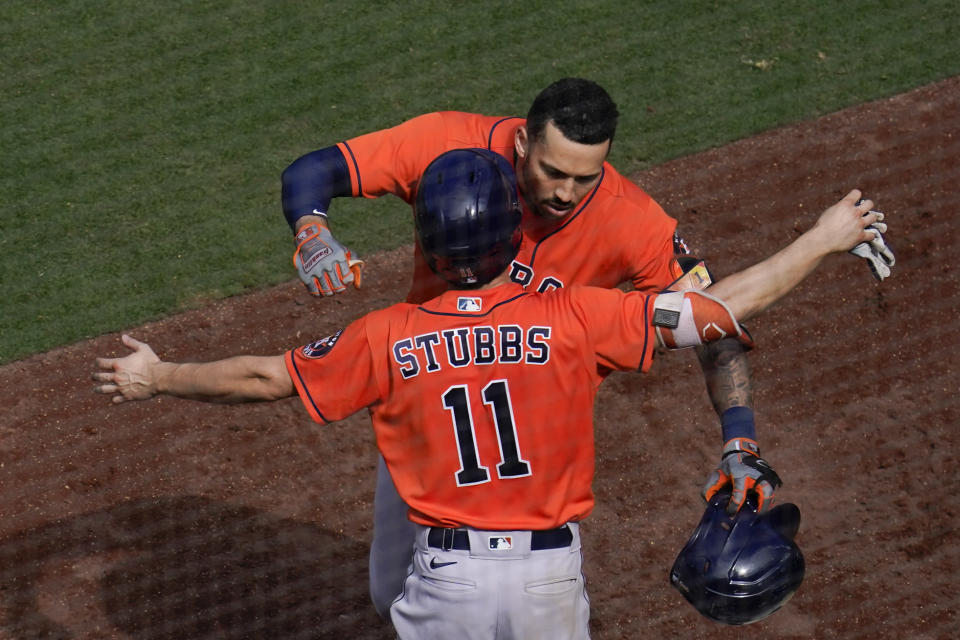 Houston Astros' Carlos Correa, above, is greeted by teammate Garrett Stubbs (11) after hitting a home run during the seventh inning of a baseball game against the San Diego Padres, Sunday, Sept. 5, 2021, in San Diego. (AP Photo/Gregory Bull)
