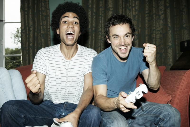 Two young men pump their fists in jubilation while sitting on a couch and holding game controllers.