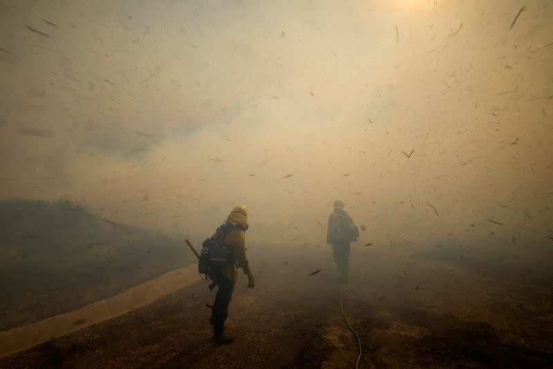Firefighters face strong winds as they head up a hillside to battle a wind driven wildfire near Irvine, California