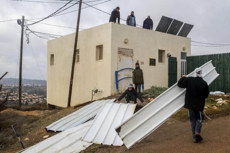 Israeli settlers block the entrance to the the settlement outpost of Amona, in the Israeli-occupied West Bank, on December 15, 2016