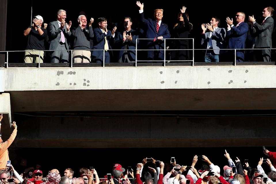 U.S. President Donald Trump and first lady Melania Trump wave to the crowd during a game between LSU and Alabama (Reuters)