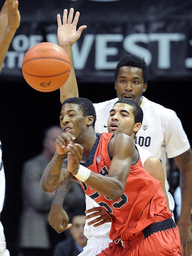 Utah;'s Delon Wright, foreground, gets a pass away as Colorado's Xavier Talton, center, and Wesley Gordon defend during the first half of an NCAA college basketball game Saturday, Feb. 1, 2014, in Boulder, Colo. (AP Photo/The Daily Camera, Cliff Grassmick)