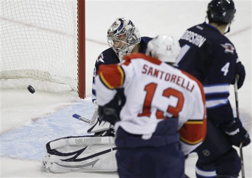 Winnipeg Jets goaltender Ondrej Pavelec, left, watches the puck float past after Florida Panthers' Mike Santorelli (13) scores during the second period of NHL hockey game action in Winnipeg, Manitoba, Thursday, Nov. 10, 2011. (AP Photo/The Canadian Press, Trevor Hagan)