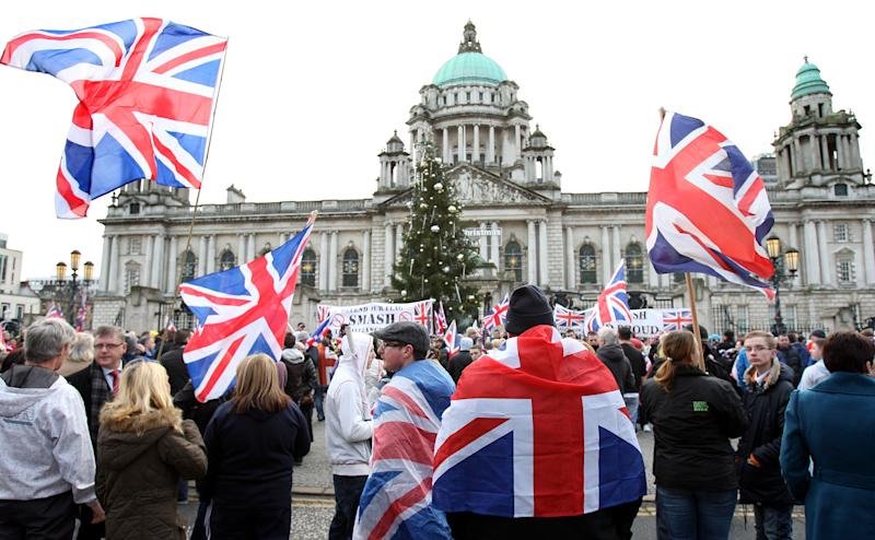 Protestant Loyalist protestors converge on Belfast city hall Saturday Jan. 5, 2013. Ongoing protests and demonstrations continue at the removal of the Union flag from the Belfast city hall. Police said Saturday that more than 30 petrol bombs were thrown at officers, along with ball bearings, fireworks and bricks as they responded to clashes Friday night in Protestant sections of Belfast. Friday's clashes come a day after 10 police were injured in east Belfast during a similar demonstration. (AP Photo/Paul Faith/PA) UNITED KINGDOM OUT