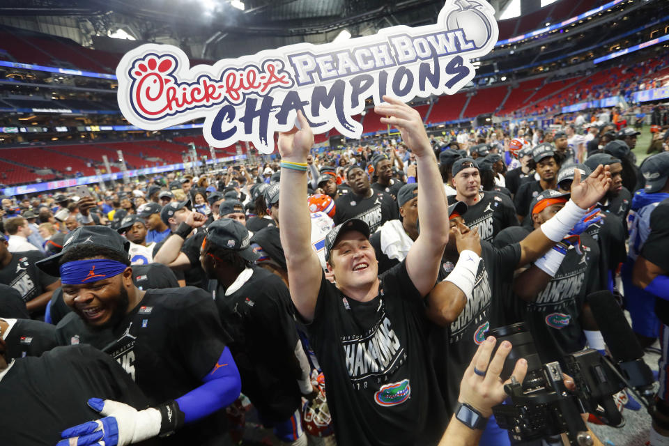 FILE - In this Dec. 29, 2018, file photo, Florida players celebrate after the Peach Bowl NCAA college football game against Michigan in Atlanta. The Peach Bowl is donating $1.09 million to help fund COVID-19 screenings in Georgia. The bowl announced it will help fund the telemedicine screening mobile app developed by Augusta University Health System. The AU Health ExpressCare app allows for free virtual screenings for the virus throughout the day with no appointment. (AP Photo/John Bazemore, File)