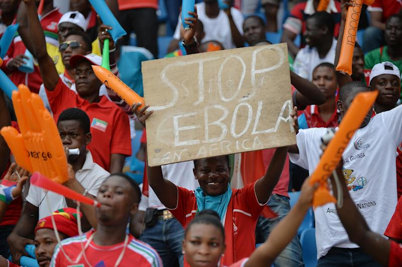 """A football fan holds a sign reading """"Stop Ebola in Africa"""" ahead of a 2015 African Cup of Nations group A football match in Bata, Equatorial Guinea, on January 17, 2015 (AFP Photo/Khaled Desouki)"""