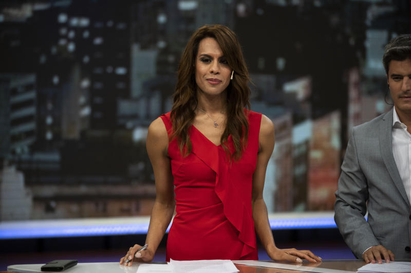 In this March 5, 2020 photo, Diana Zurco stands at the table for news anchors during a rehearsal for her debut as the country's first transgender newscaster, in Buenos Aires, Argentina. Her job as a co-anchor of Public Television's prime time evening news program is a milestone for an excluded community that is often the target of violence and has a life expectancy roughly half that of the rest of the population. (AP Photo/Victor R. Caivano)