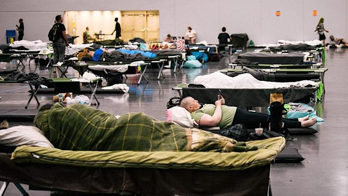 People rest at the Oregon Convention Center cooling station in Oregon, Portland