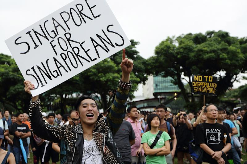 SINGAPORE - FEBRUARY 16: A man reacts to a speaker during the protest against the government's White Paper on Population at Speakers' Corner speech at Hong Lim Park on February 16, 2013 in Singapore. Thousands of protesters gathered today following the release of a government white paper on population that revealed it could increase 30% to 6.9 million by 2030, angering residents who already see a strain on housing, transportation and healthcare. (Photo by Suhaimi Abdullah/Getty Images)
