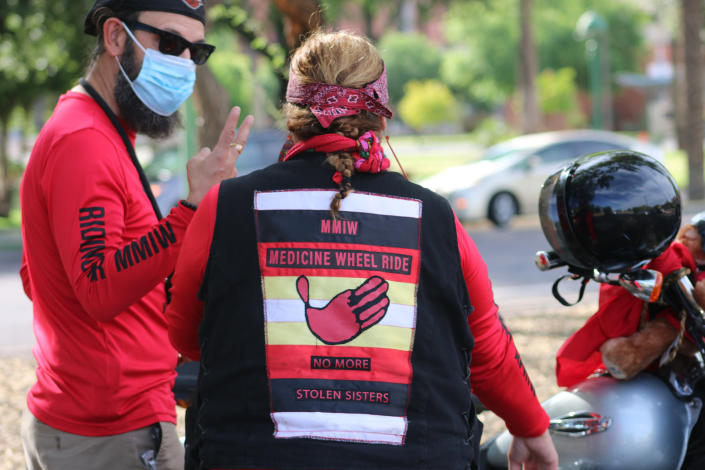 Members from Medicine Wheel Ride stand by their bikes tied with red ribbons at the Arizona State Capitol in Phoenix, Wednesday, May 5, 2021, after riding to raise awareness for missing and murdered Indigenous women and girls. (AP Photo/Cheyanne Mumphrey)