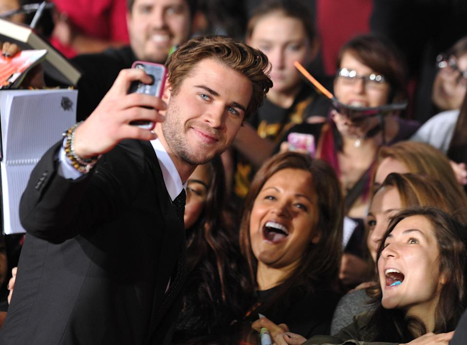 """FILE - In this Monday, Nov. 18, 2013 file photo, Liam Hemsworth poses for a photo with fans as he arrives at the Los Angeles premiere of """"The Hunger Games: Catching Fire"""" at Nokia Theatre LA Live. Hemsworth's popularity amplified after he appeared in """"The Hunger Games"""" in 2012. (Photo by Jordan Strauss/Invision/AP, File)"""