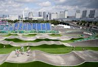 <p>TOPSHOT - Cyclists compete in the cycling BMX racing men's quarter-finals run at the Ariake Urban Sports Park during the Tokyo 2020 Olympic Games in Tokyo on July 29, 2021. (Photo by Lionel BONAVENTURE / AFP) (Photo by LIONEL BONAVENTURE/AFP via Getty Images)</p>