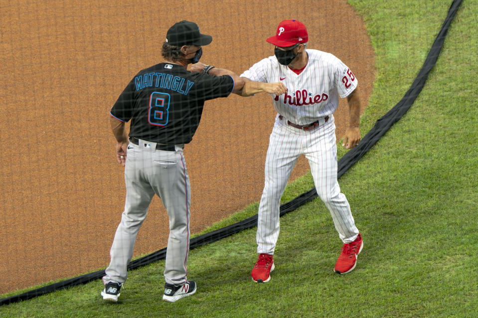 Miami Marlins manager Don Mattingly, left, gives an elbow-bump to Philadelphia Phillies manager Joe Girardi, right, prior to a baseball game, Friday, July 24, 2020, in Philadelphia. (AP Photo/Chris Szagola)