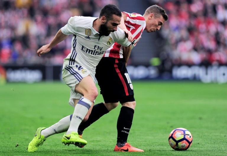 Real Madrid's defender Daniel Carvajal (L) vies with Athletic Bilbao's forward Iker Muniain during the Spanish league football match March 18, 2017