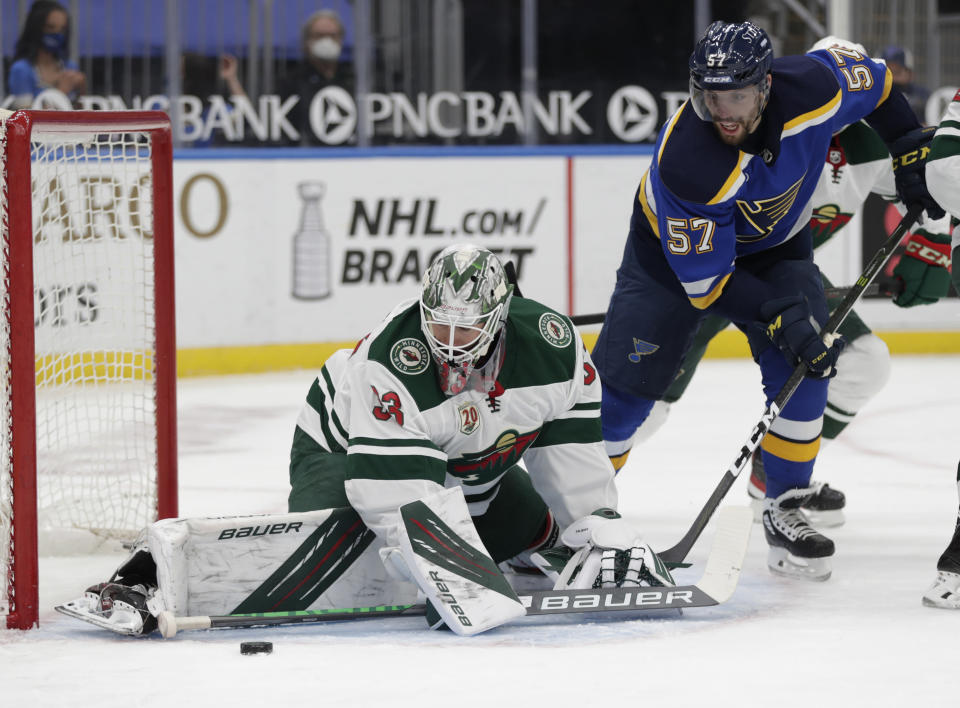 Minnesota Wild goaltender Cam Talbot (33) makes a stick save as St. Louis Blues' David Perron (57) looks for the loose puck in the second period of an NHL hockey game, Wednesday, May 12, 2021 in St. Louis. (AP Photo/Tom Gannam)