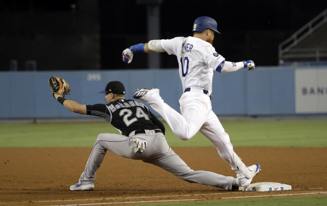 Los Angeles Dodgers' Justin Turner, right, is safe at first base on a fielder's choice next to Colorado Rockies first baseman Ryan McMahon during the third inning of a baseball game Wednesday, Sept. 4, 2019, in Los Angeles. (AP Photo/Marcio Jose Sanchez)
