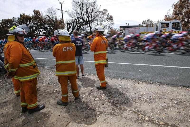 Members of the Country Fire Service cheer the riders en route between Woodside and Stirling on stage 2
