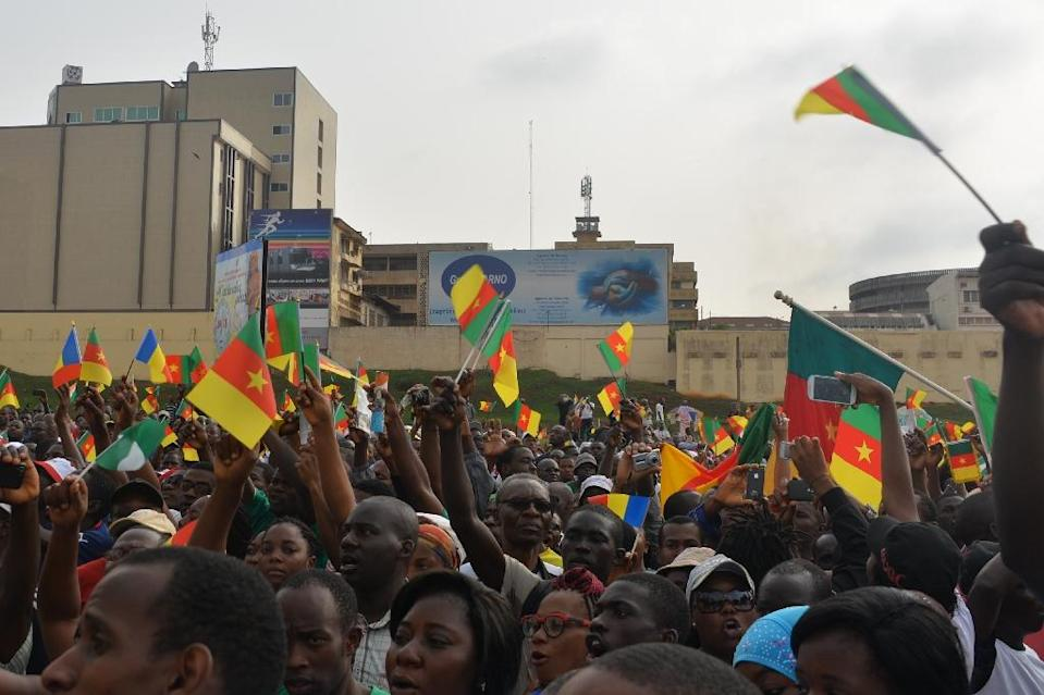 People wave Cameroon's national flag as they take part in a demonstration on February 28, 2015, in downtown Yaounde, against Islamist group Boko Haram (AFP Photo/Reinnier Kaze)