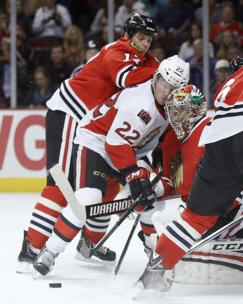 Ottawa Senators right wing Erik Condra (22) is unable to get a shot on goal against Chicago Blackhawks defenseman Sheldon Brookbank (17) and goalie Nikolai Khabibulin during the first period of an NHL hockey game Tuesday, Oct. 29, 2013, in Chicago. (AP Photo/Charles Rex Arbogast)