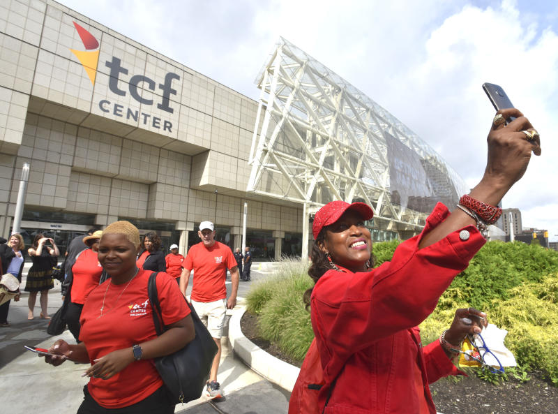 Gina Peoples, right, of Detroit, a volunteer with The Parade Company, takes a selfie in front of the newly named TCF Center in downtown Detroit Tuesday, Aug. 27, 2019. Politicians, executives and VIPs gathered at what had been known as Cobo Center since 1960 for the renaming announcement. (Todd McInturf /Detroit News via AP)