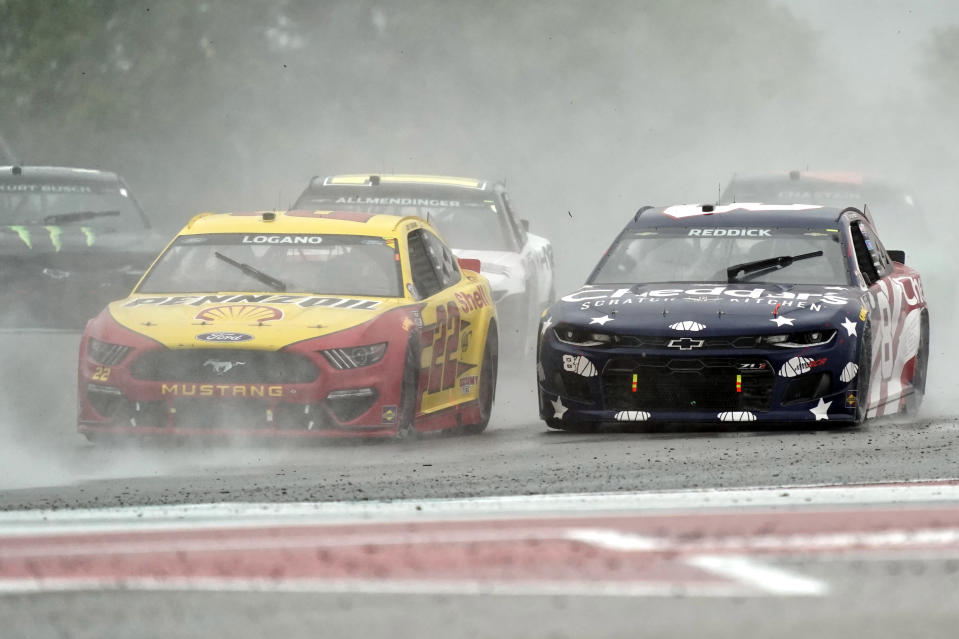 Joey Logano (22) and Tyler Reddick (8) lead other cars out of Turn 18 during the NASCAR Cup Series auto race at the Circuit of the Americas in Austin, Texas, Sunday, May 23, 2021. (AP Photo/Chuck Burton)