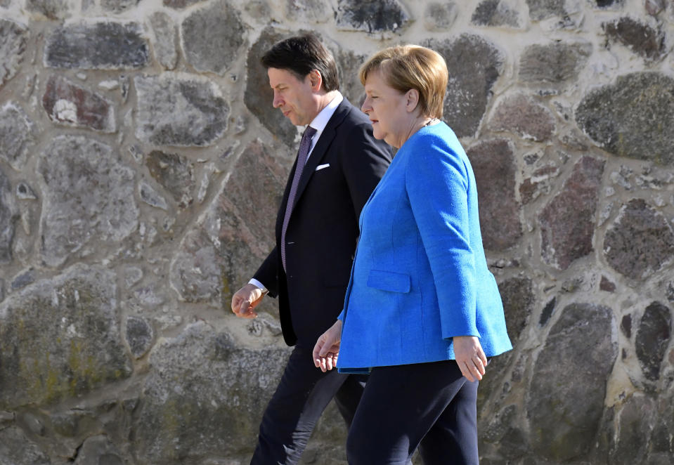 FILE - In this Monday, July 13, 2020 filer, German Chancellor Angela Merkel and Italian Prime Minister Giuseppe Conte walk to attend a press conference in the garden of the German governmental guest house in Meseberg, outside Berlin. When Giuseppe Conte exited the premier's office, palace employees warmly applauded in him appreciation. But that's hardly likely to be Conte's last hurrah in politics. Just a few hours after the handover-ceremony to transfer power to Mario Draghi, the former European Central Bank chief now tasked with leading Italy in the pandemic, Conte dashed off a thank-you note to citizens that sounded more like an ''arrivederci″ (see you again) then a retreat from the political world he was unexpectedly propelled into in 2018. (Tobias Schwarz/Pool photo via AP)