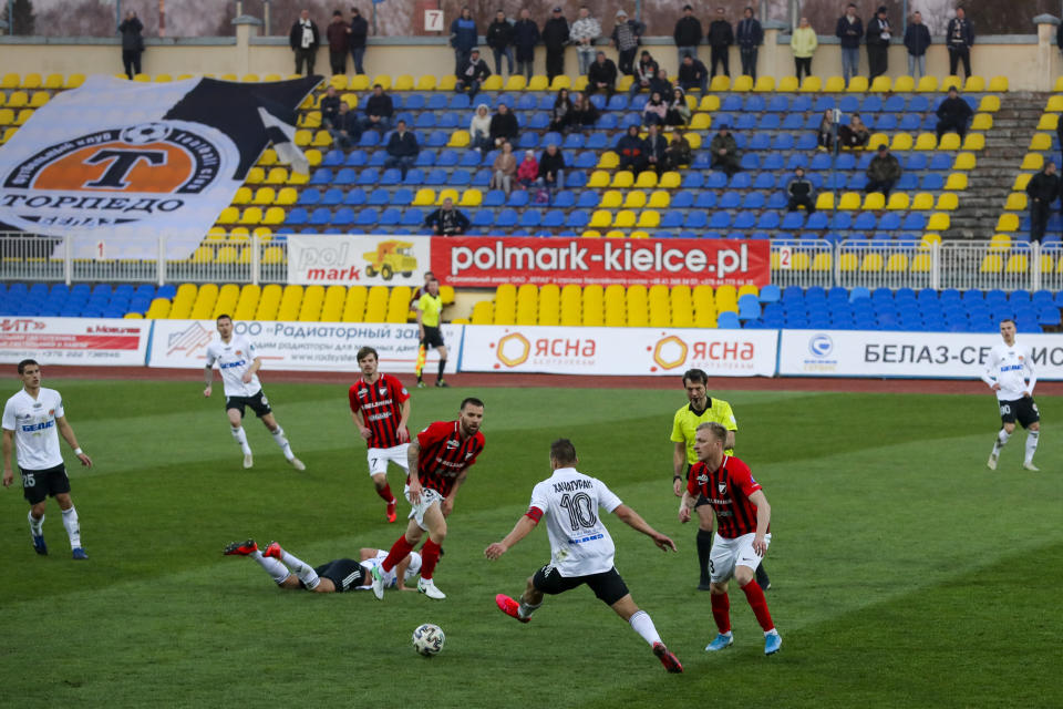 In this photo taken on Friday, March 27, 2020, players in action during the Belarus Championship soccer match between Torpedo-BelAZ Zhodino and Belshina Bobruisk in the town of Zhodino, Belarus. Longtime Belarus President Alexander Lukashenko is proudly keeping soccer and hockey arenas open even though most sports around the world have shut down because of the coronavirus pandemic. The new coronavirus causes mild or moderate symptoms for most people, but for some, especially older adults and people with existing health problems, it can cause more severe illness or death. (AP Photo/Sergei Grits)